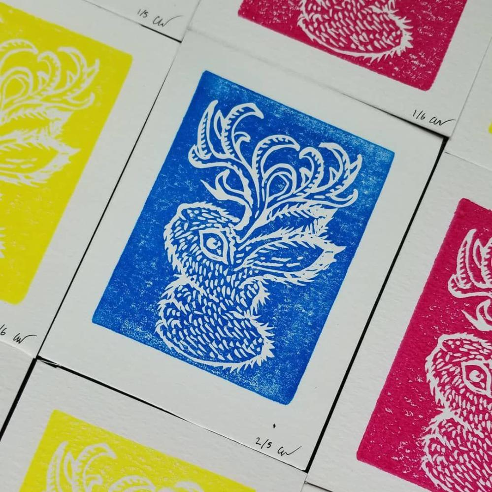 Prints of a jackalope create a pattern of fluorescent colors.